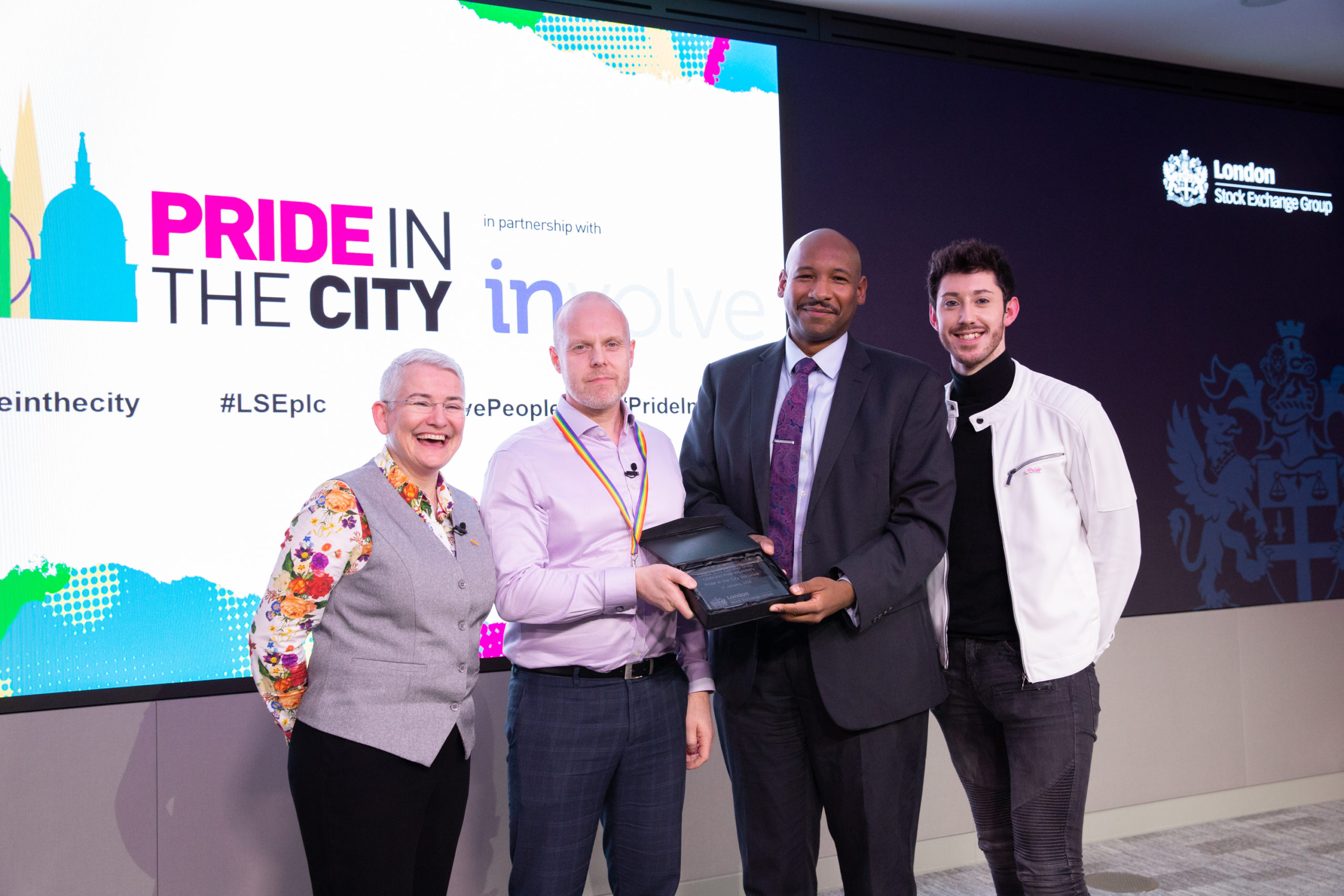 Four people handing over award